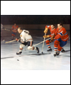 Bobby Hull skating away from two Montreal Canadiens with the puck